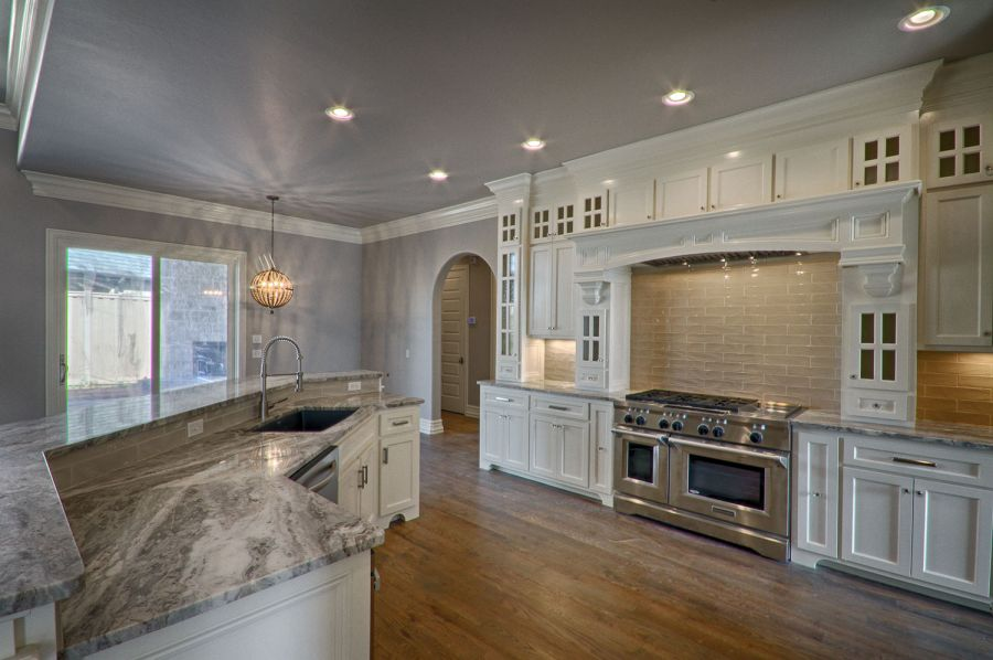Elegant kitchen with gray counter tops and white cabinets with tile backsplash.