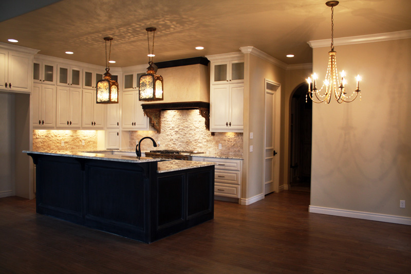 Luxury kitchen with elegant backsplash and granite counter tops. White cabinets that go all the way to the ceiling.