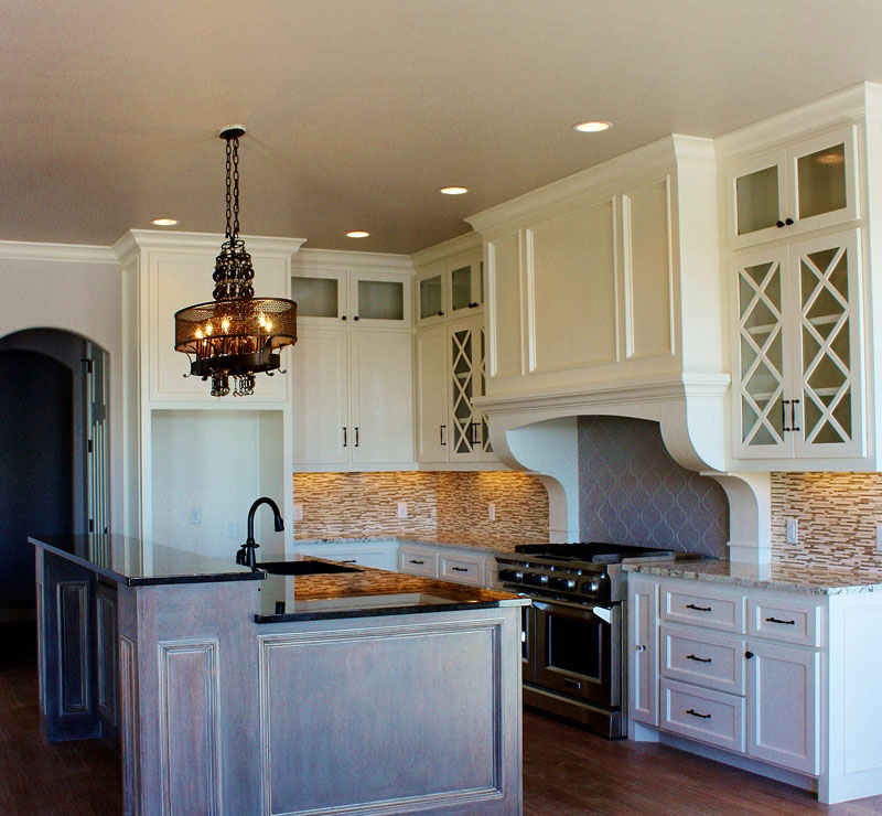 White cabinetry with detailed tiled backsplash in kitchen.