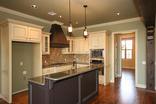 Brown and white cabinets with high island seating area in the kitchen.