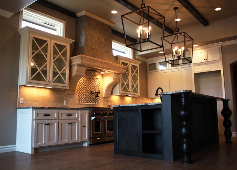 Black and white kitchen cabinets with huge chandlers above island.