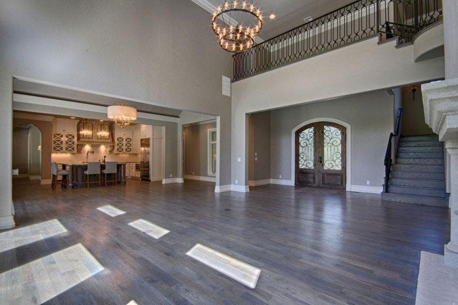 Grand living area with high ceilings next to home entrance.