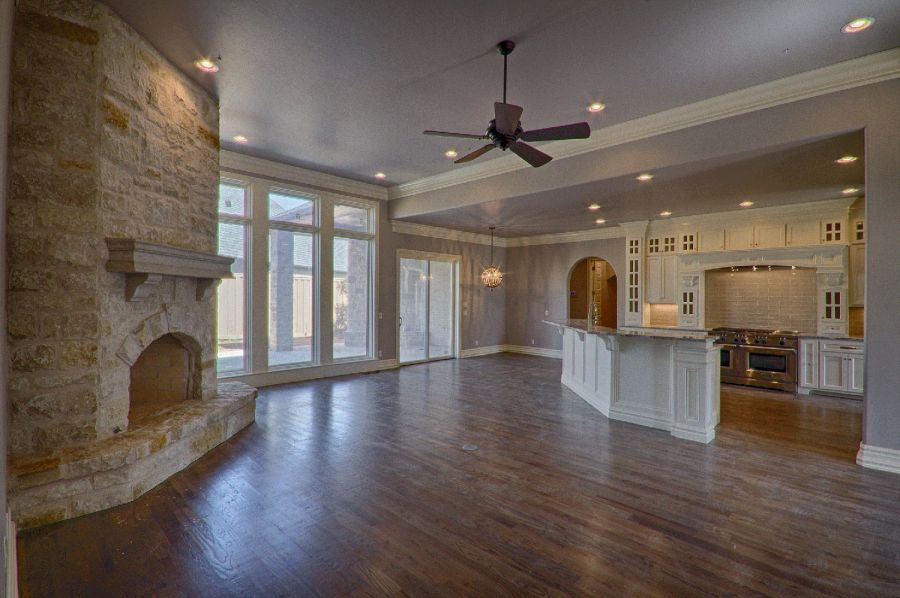 Living area with big stone fireplace and beautiful wood flooring.
